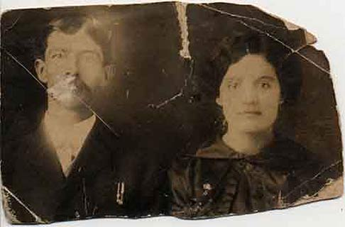 Damaged photo. Some sections are severely scratched. The man's mouth is two-thirds gone and the couple's eyes are faded and faint.